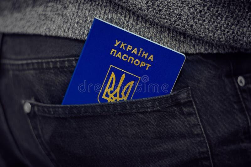 Um passaporte biométrico internacional azul de Ucrânia em um bolso de calças de brim pretas fotos de stock