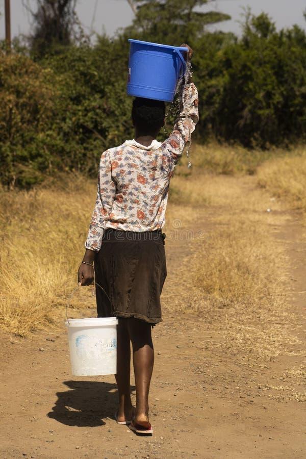 Um passeio africano da menina interurbano para buscar a água em umas cubetas fotografia de stock royalty free