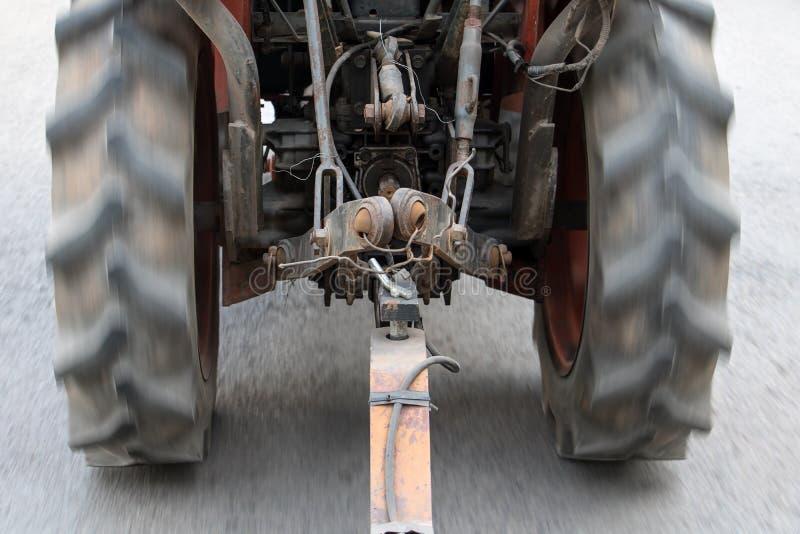 Um passeio velho do trator na estrada asfaltada e nas trações uma carga fotografia de stock royalty free