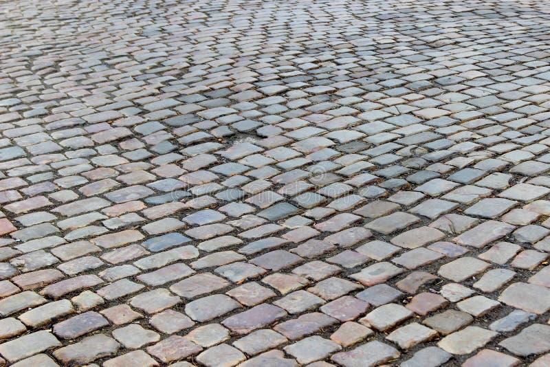 Um pavimento velho do stoneblock cobbled com blocos de pedra naturais retangulares com um furo em um lugar de uma pedra imagens de stock