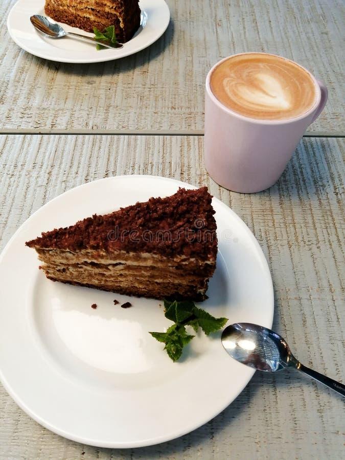 Um pedaço de bolo em uma placa branca em uma tabela em um café perto de um cappuccino da xícara de café foto de stock royalty free