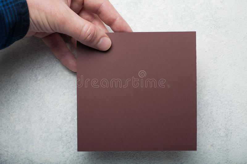 Um pedaço de papel quadrado marrom em uma mão europeia em um fundo branco do vintage fotos de stock