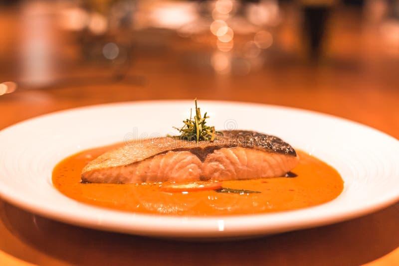 Um peixe dos salmões com caril no prato no jantar da tabela imagens de stock royalty free
