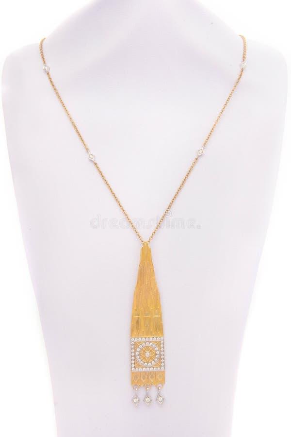 Um pendente étnico feito do metal do ouro em uma corrente longa do ouro imagem de stock