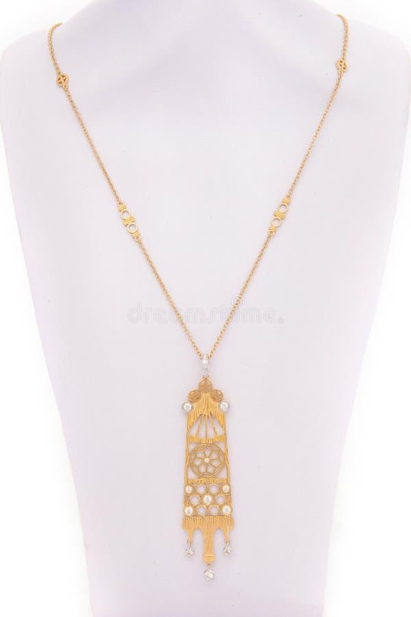 Um pendente étnico feito do metal do ouro em uma corrente longa do ouro fotos de stock royalty free