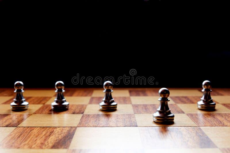 Um penhor da xadrez está para fora do outro Conceito da liderança do negócio foto de stock