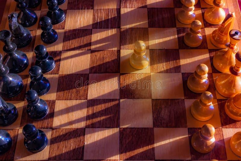 Um penhor que fica contra o conjunto completo de partes de xadrez pretas Close up do tabuleiro de xadrez com partes de madeira na fotos de stock royalty free