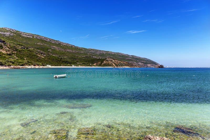 Um pequeno barco numa surpreendente praia de água azul em Portugal imagens de stock