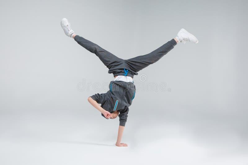 Um pequeno desportivo com bom treinamento físico, dança que está em uma mão em um fundo cinzento foto de stock royalty free