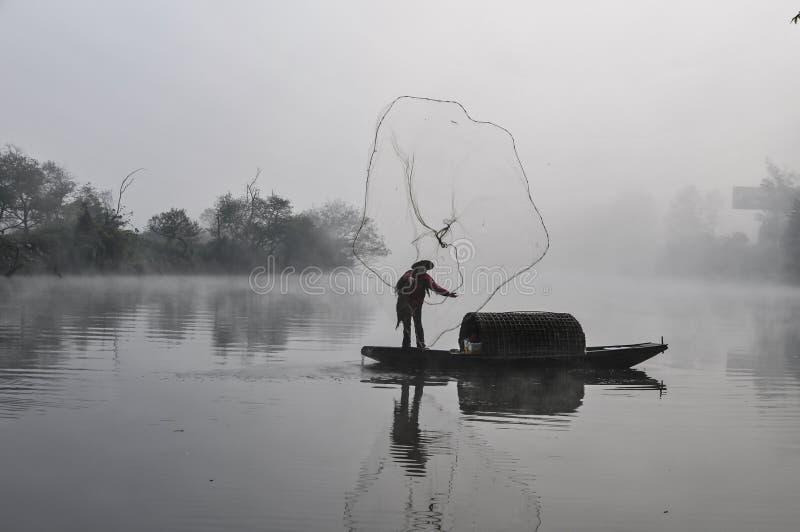 Um pescador asiático com trabalhos tradicionais e antigos da rede e do barco de pesca na manhã enevoa-se fotografia de stock royalty free