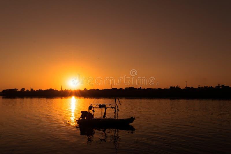 Um pescador com seu barco que vai para trás casa em um por do sol dourado imagem de stock