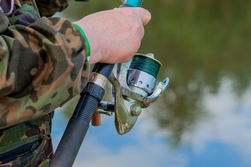 Um pescador com uma vara de pesca Close-up de uma m?o que guarda uma haste de giro e tor??o de uma bobina Vista colorida, fundo b fotos de stock