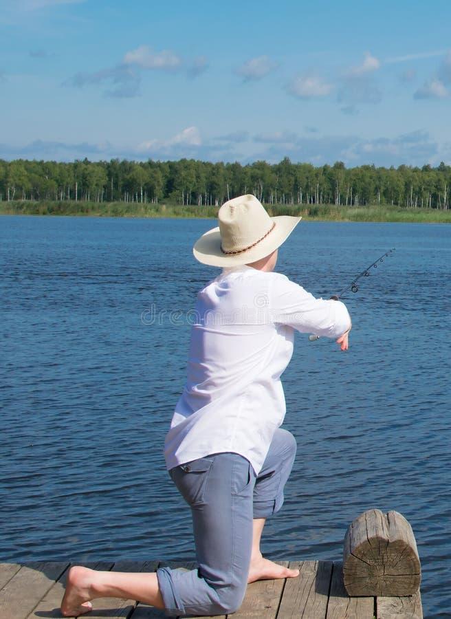 Um pescador em um chapéu, um homem, joga uma vara de pesca no rio para pescar foto de stock royalty free
