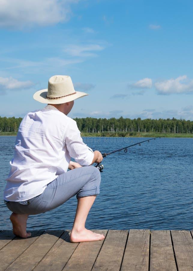 Um pescador está sentando-se em um cais com uma vara de pesca que espera um peixe grande para morder imagem de stock