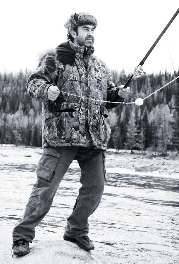 Um pescador no rio no inverno fotos de stock royalty free