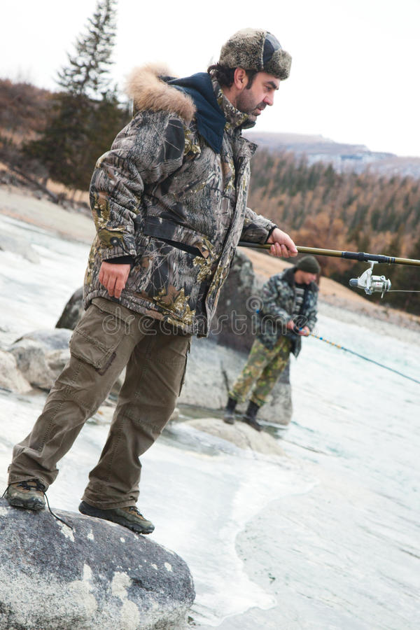 Um pescador no rio no inverno imagem de stock