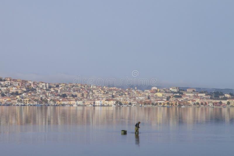 Um pescador no trabalho que dobra-se na água do mar lisa que reflete as casas de Sant 'Antioco em Sardinia foto de stock