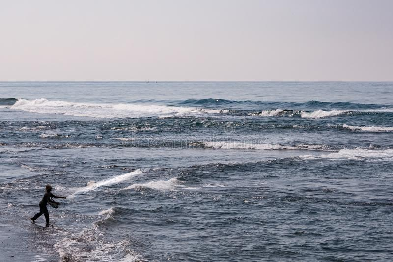 Um pescador que molda sua rede da praia imagens de stock royalty free