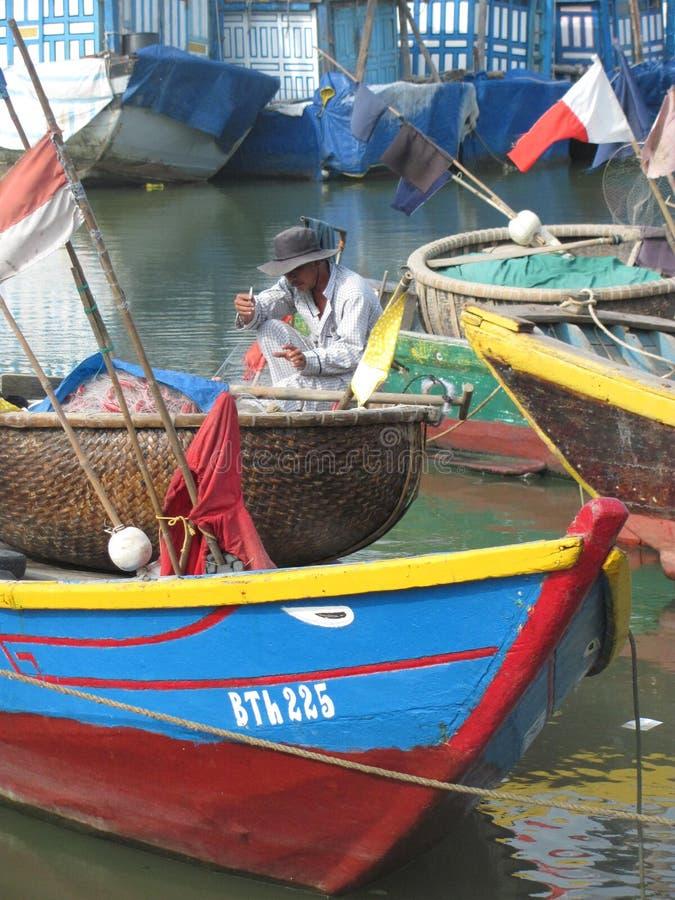 Um pescador repara a rede da pesca fotografia de stock royalty free