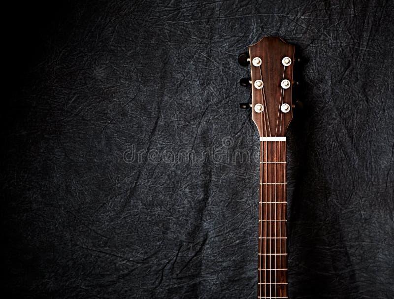 Um pescoço da guitarra acústica no fundo escuro de pano imagem de stock royalty free