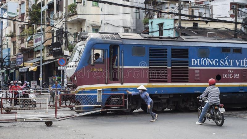 Um pessoal fêmea da porta reabre a estrada enquanto um trem cruza a rua em Ho Chi Minh City, Vietname imagem de stock royalty free
