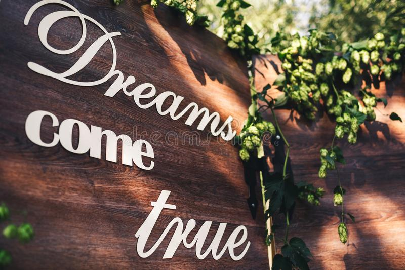 Um photozone de madeira, decorado com lúpulos, com a inscrição: Os sonhos do ` vêm verdadeiro ` imagens de stock royalty free