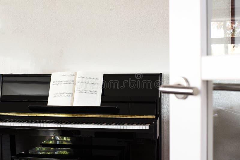 Um piano preto em uma sala de visitas branca moderna com folhas de música foto de stock royalty free
