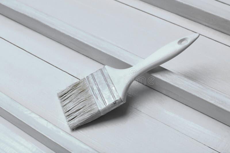 Um pincel branco em uma superfície de madeira branca imagem de stock royalty free