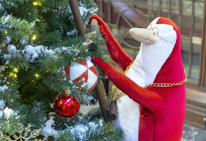 Um pinguim vermelho e branco escala as escadas à árvore de Natal fotos de stock royalty free