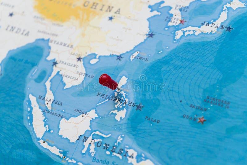 Um pino em manila, Filipinas no mapa do mundo imagem de stock