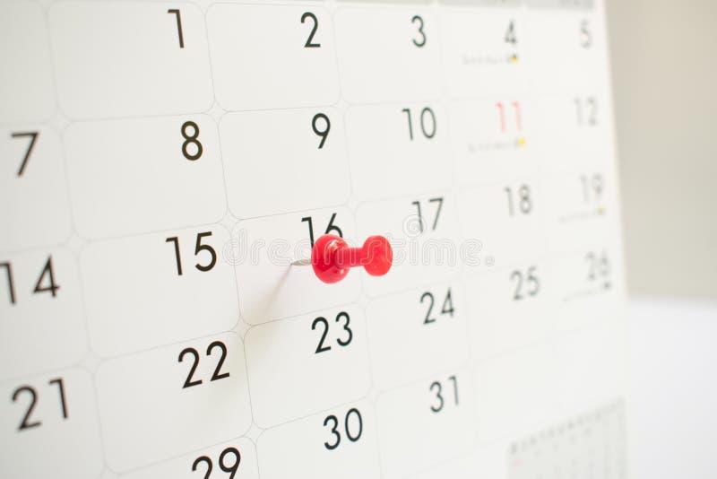 Um pino vermelho no calendário do evento fundo, fim acima, tempo fotografia de stock