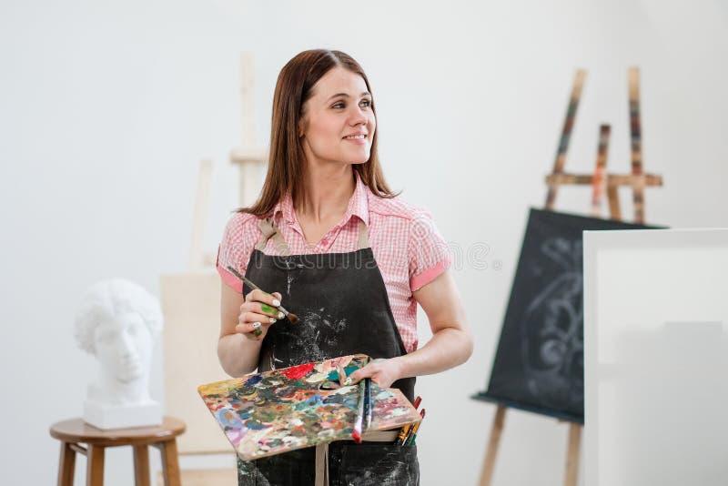 Um pintor da jovem mulher em um estúdio branco brilhante tira uma imagem na lona em uma armação foto de stock royalty free