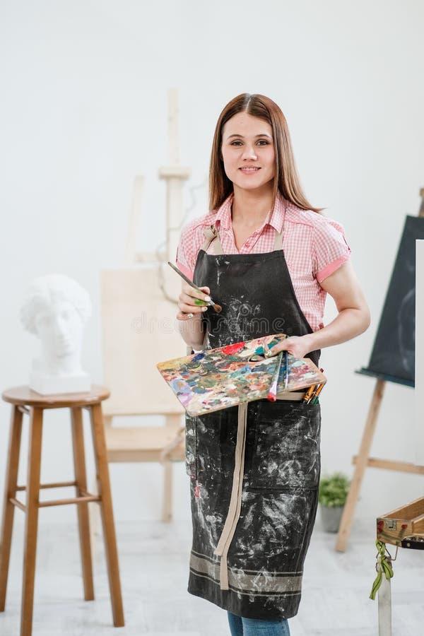 Um pintor da jovem mulher em um estúdio branco brilhante tira uma imagem na lona em uma armação fotografia de stock royalty free