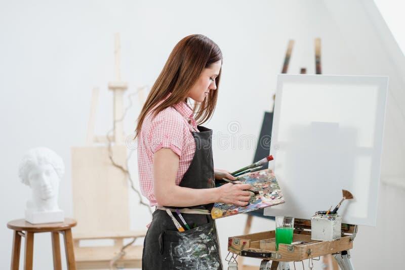 Um pintor da jovem mulher em um estúdio branco brilhante tira uma imagem na lona em uma armação imagens de stock royalty free