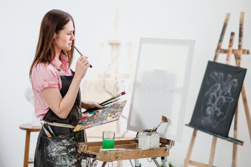 Um pintor da jovem mulher em um estúdio branco brilhante tira uma imagem na lona em uma armação fotos de stock royalty free