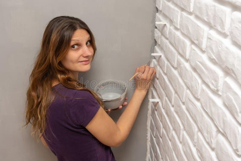 Um pintor de casa pinta um canto cinzento da parede com uma borla pequena fotos de stock