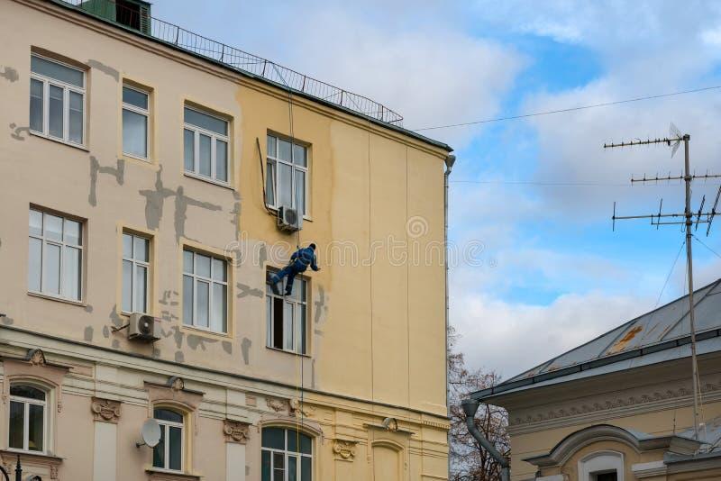 Um pintor de trabalho - um alpinista está pintando uma construção residencial foto de stock royalty free