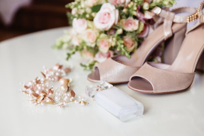 Um plano da degradação colheu o quadro, perfume da noiva, joia para o penteado do casamento, brincos e com os pés descalços em um foto de stock