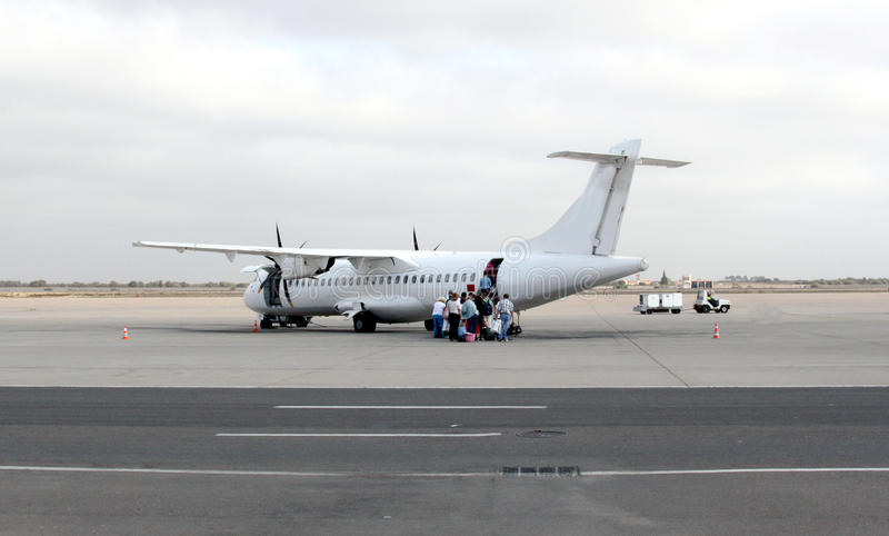 Um plano e passageiros na pista de decolagem foto de stock