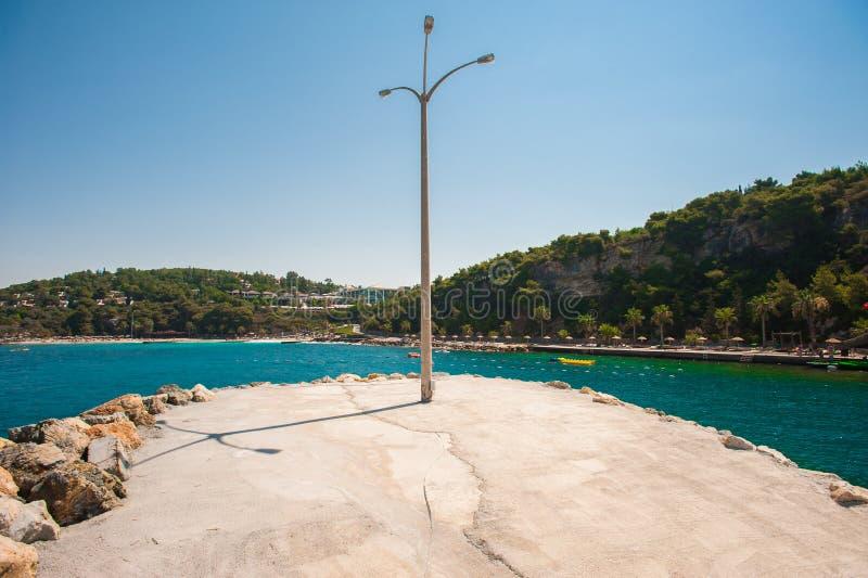 Um polo com uma lanterna na praia retroiluminada pelo mar imagens de stock royalty free