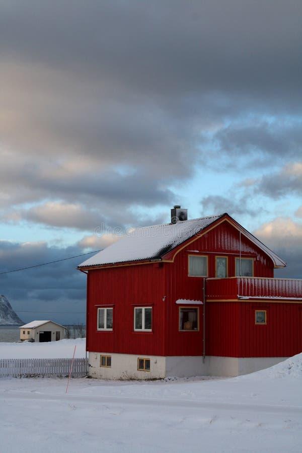 Um ponto de vista da balsa das casas cobertas com a neve em Lofoten ilha-Noruega foto de stock royalty free