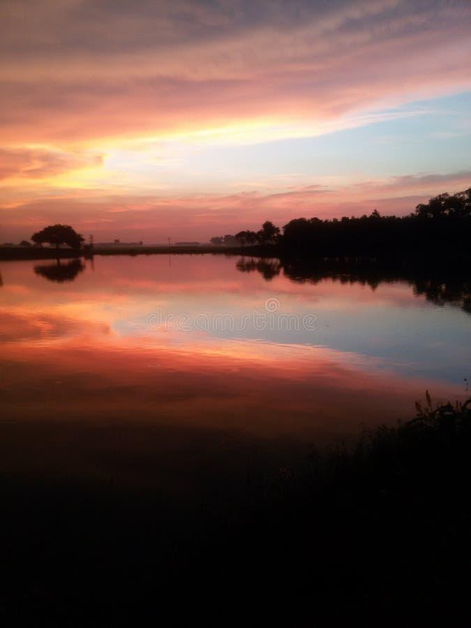 Um por do sol bonito em um lago da vila imagem de stock