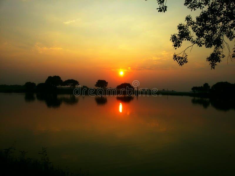 Um por do sol bonito em um lago da vila imagem de stock royalty free