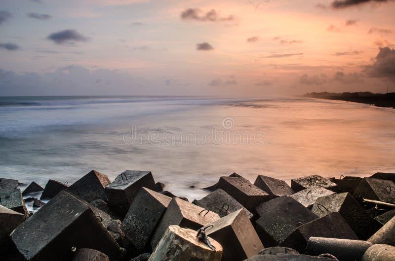 Um por do sol bonito na praia do glagah, com rocha-quebra das ondas no progo do kulon, Yogyakarta, Indonésia, Ásia fotografia de stock