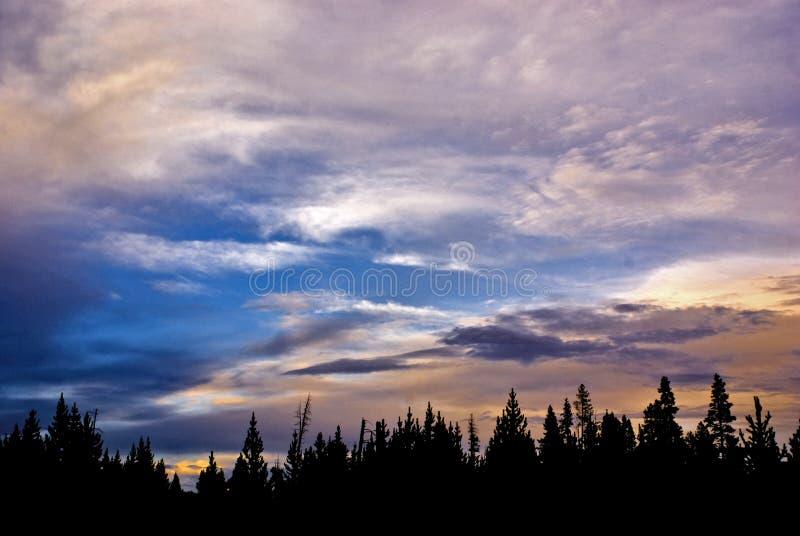 Um por do sol cor-de-rosa, alaranjado, e azul bonito sobre Wyoming florestado, sereno fotografia de stock royalty free