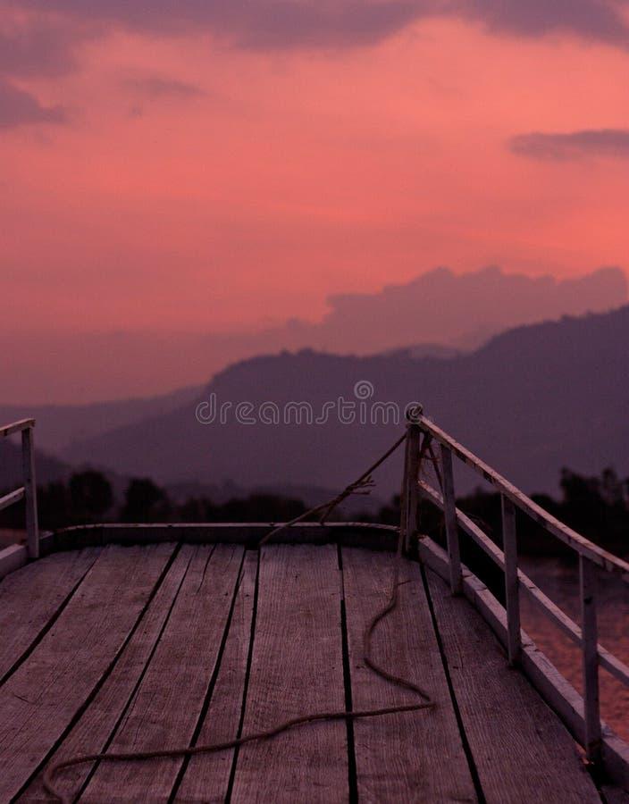 Um por do sol cor-de-rosa com um rio e as montanhas como visto de um barco em um cruzeiro em um rio de Preaek Tuek Chhu perto de  foto de stock