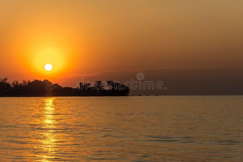 Um por do sol dourado dramático com o sol apenas aproximadamente a ajustar-se atrás da fotografia de stock