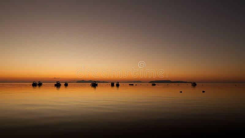 Um por do sol morno em uma água calma, com as ilhas no fundo imagem de stock