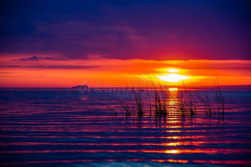 Um por do sol raramente bonito do fogo pelo mar Por do sol no golfo Por do sol no mar imagem de stock