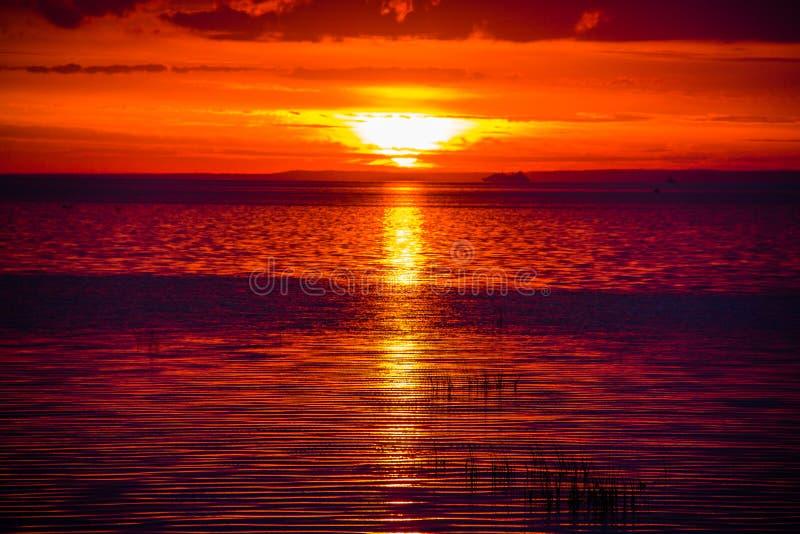 Um por do sol raramente bonito do fogo pelo mar Por do sol no golfo Por do sol no mar imagens de stock